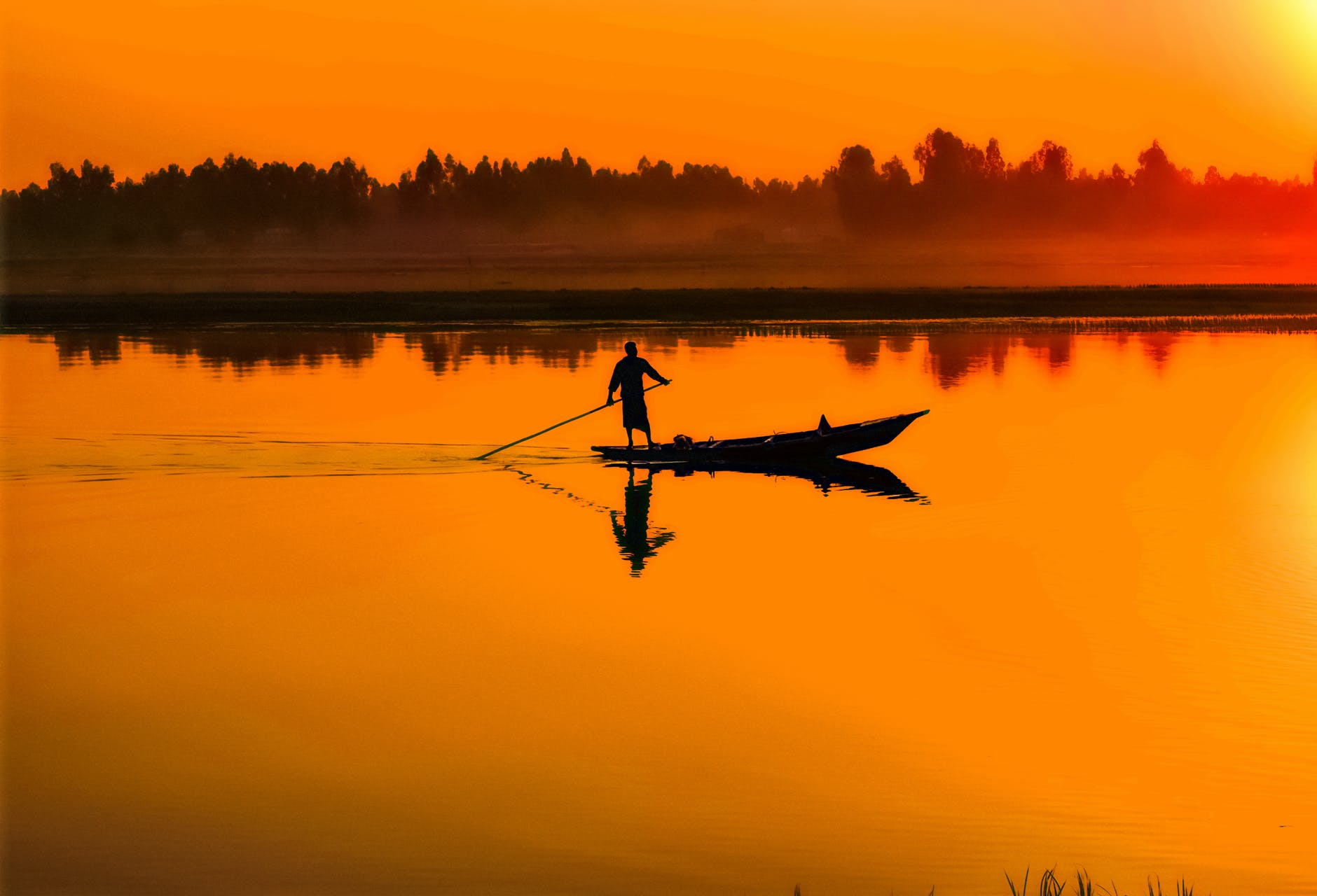 silhouette of man standing on boat in the middle of the lake